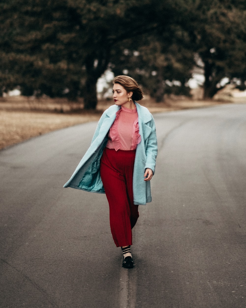 woman wearing teal coat and red pants walking on gray top road at day time