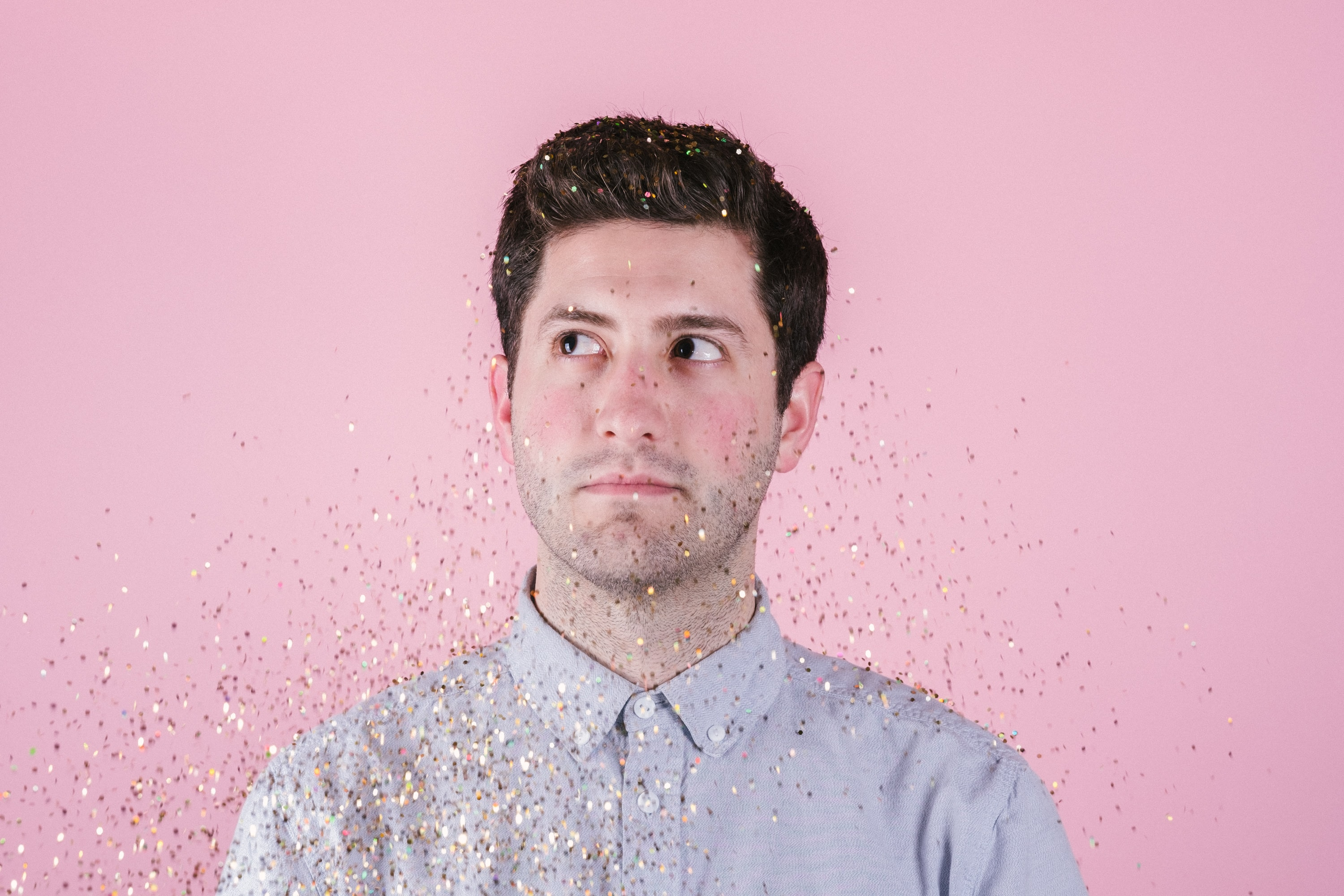 man wearing gray polo shirt behind pink background close-up photo