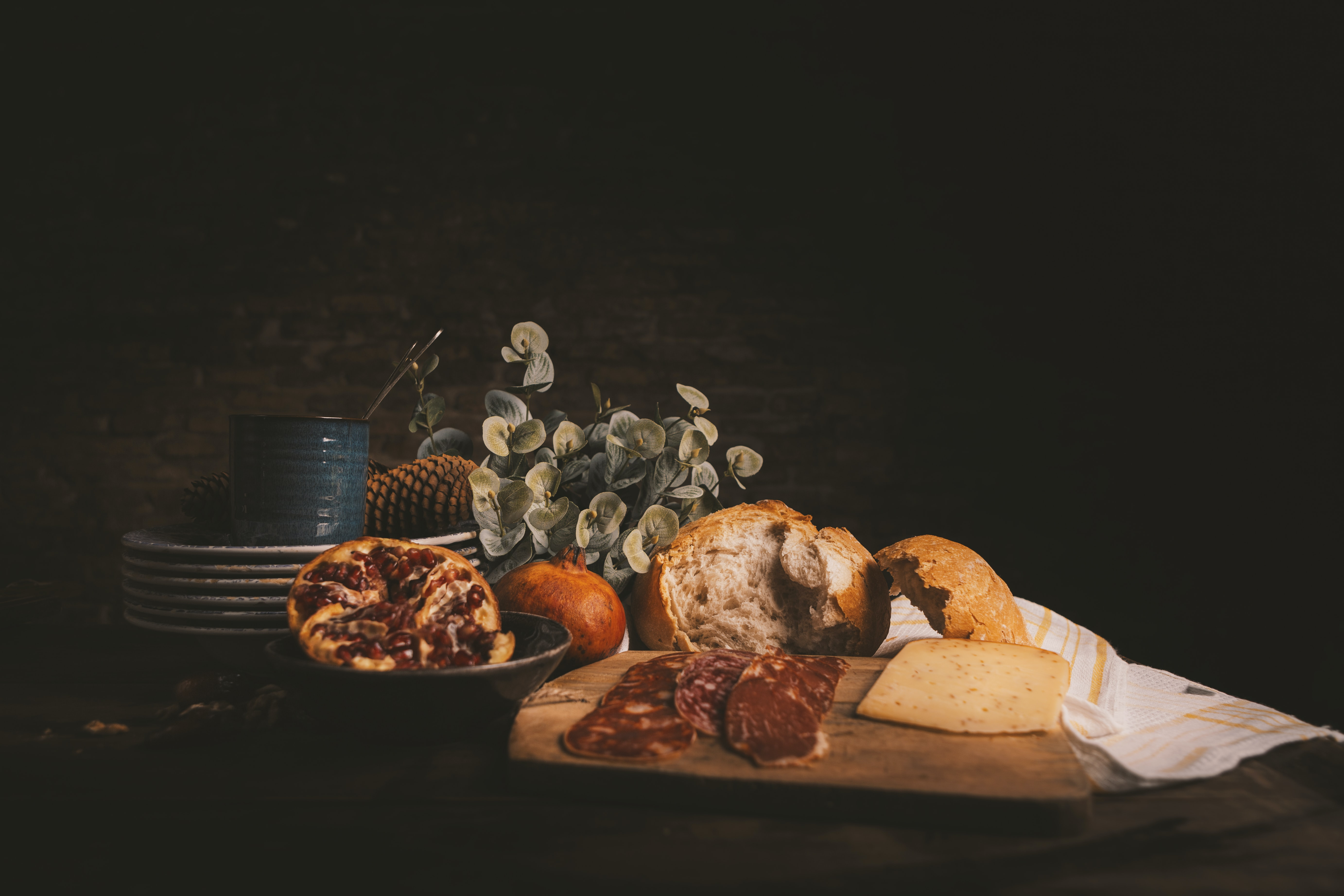 raw of meat on chopping board beside baked bread and plates on wooden table