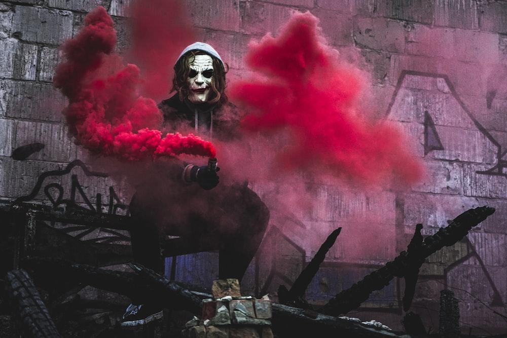 person in Joker cosplay holding smoke grenade