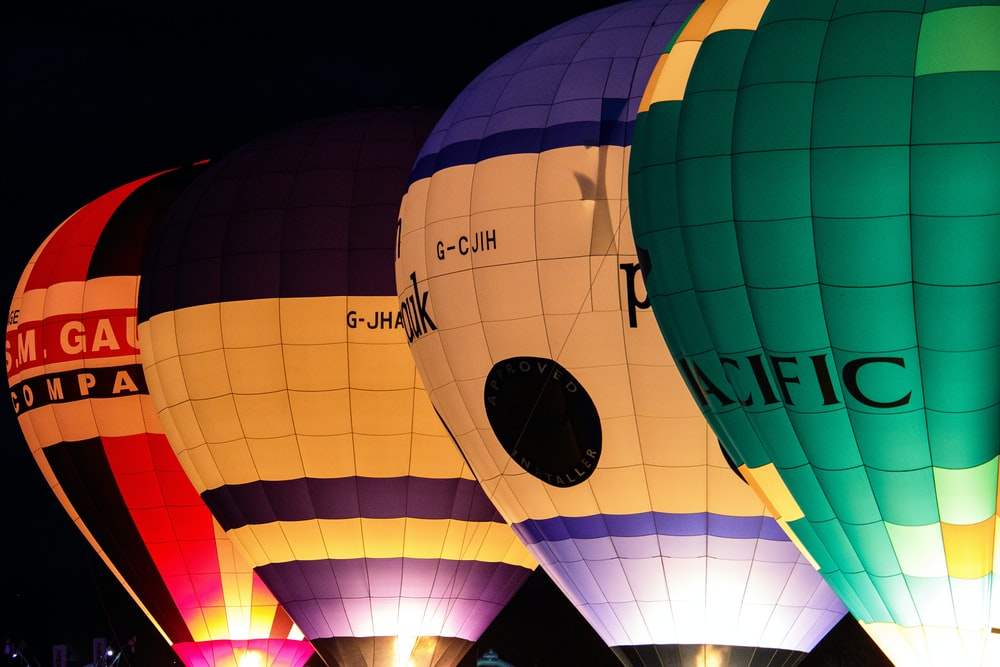 four yellow, red, and green hot air balloons