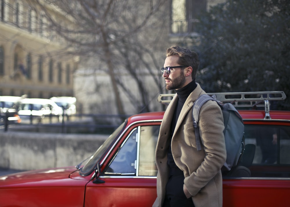 man on beige coat standing beside red car
