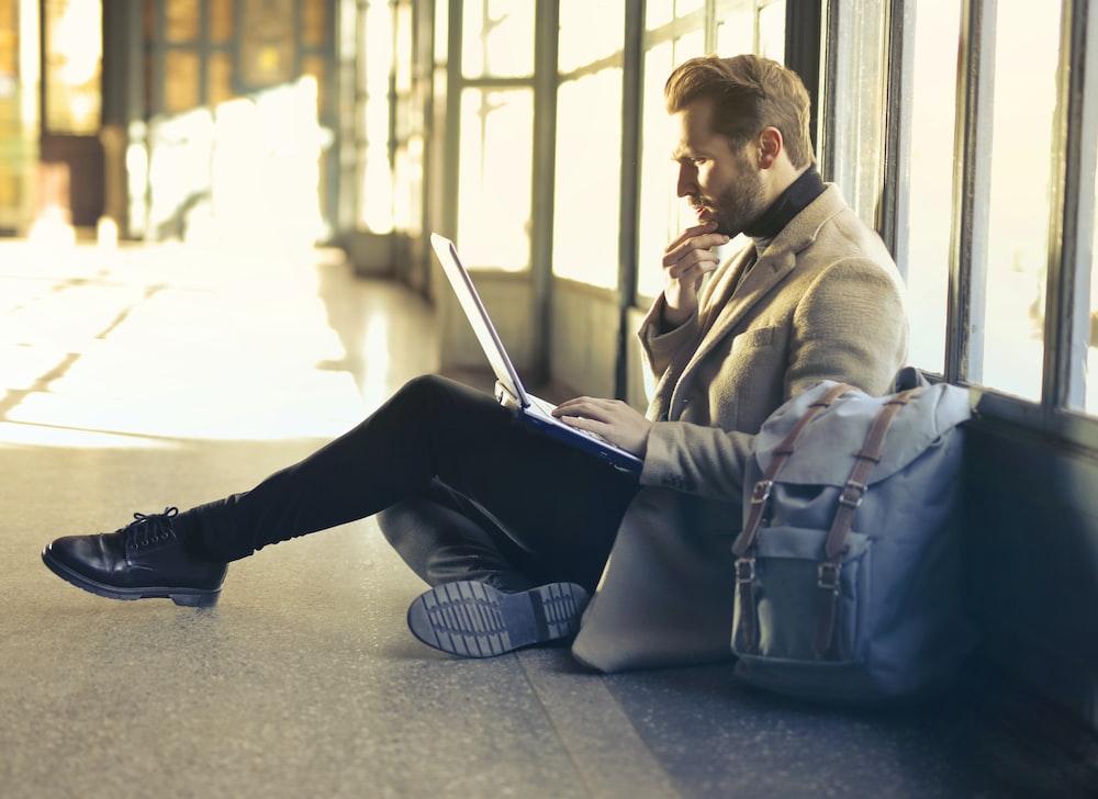man sitting on floor while using laptop