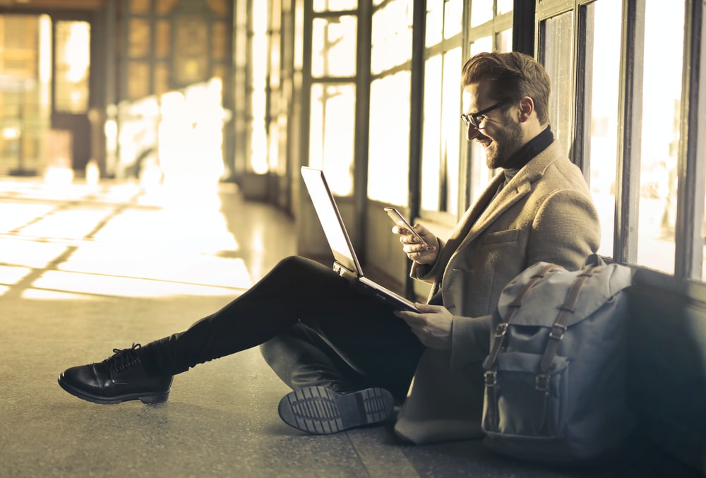 man sitting near window holding phone and laptop