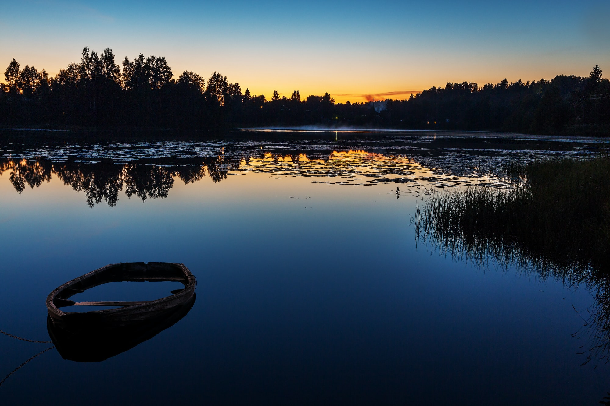 A lone boat on a lake, just before sunset.