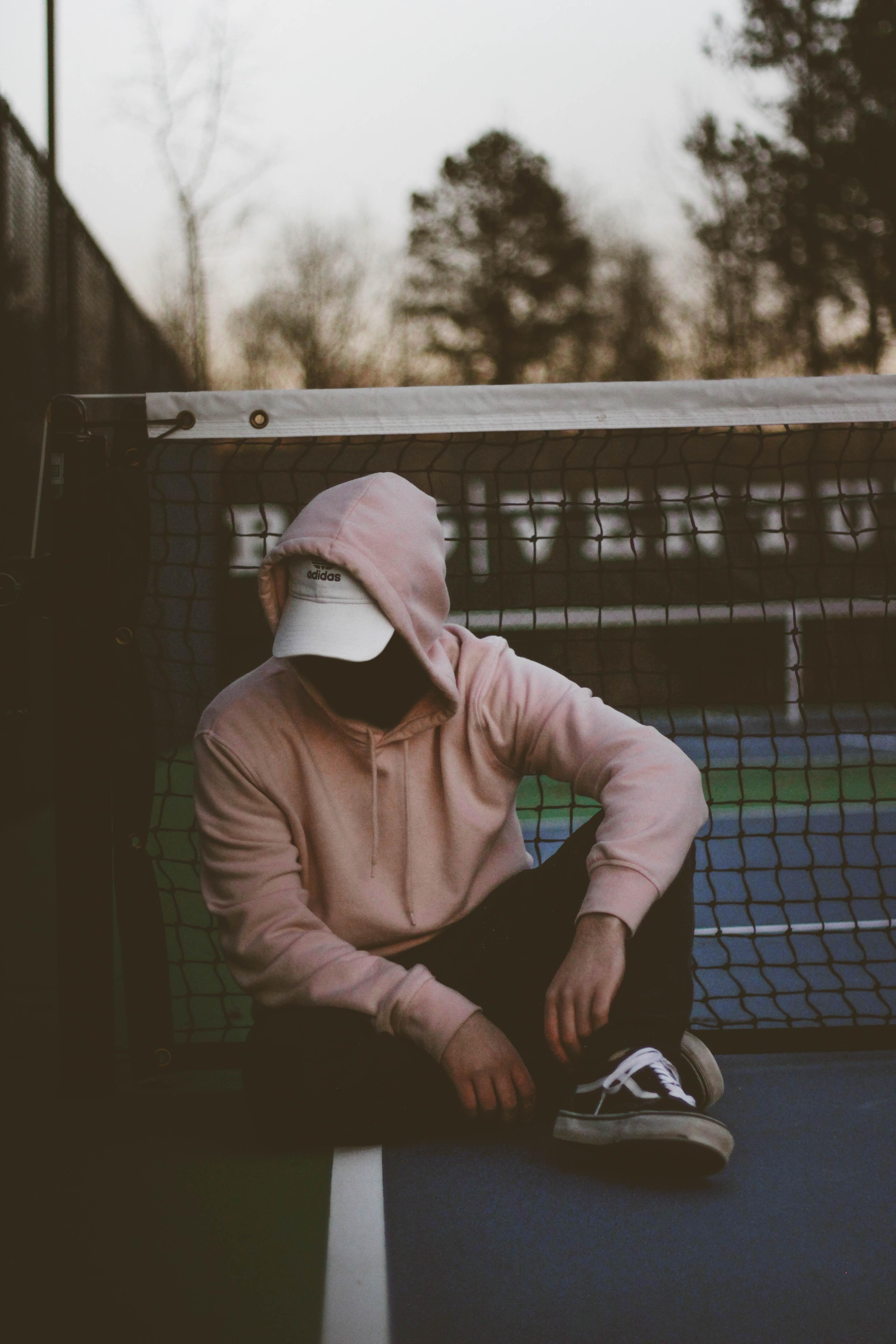 man wearing brown hoodie sitting near tennis net