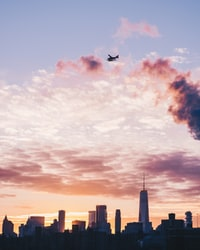 silhouette of plane flight over the city