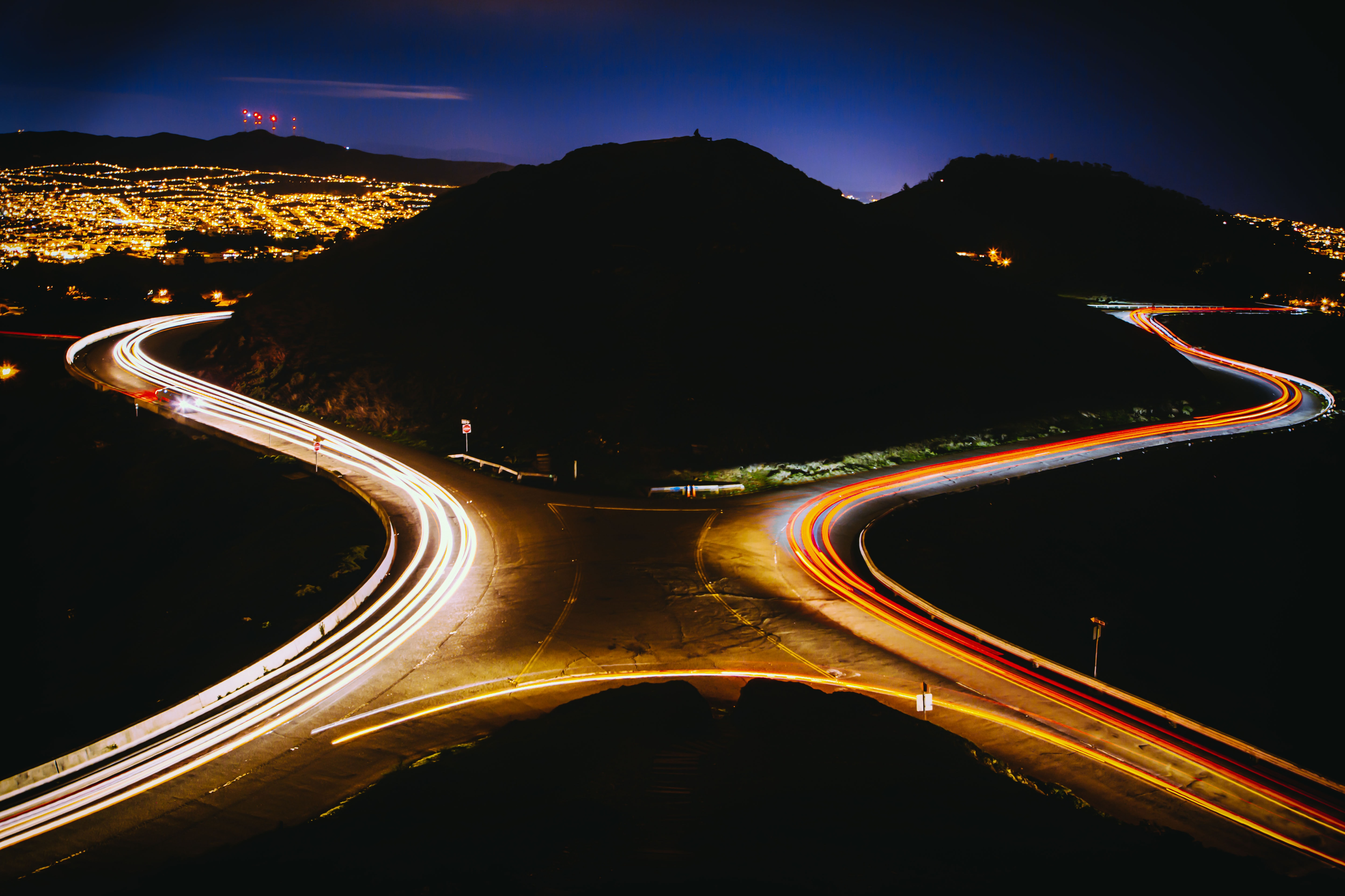 aerial view photography of cross road near mountain during nighttime