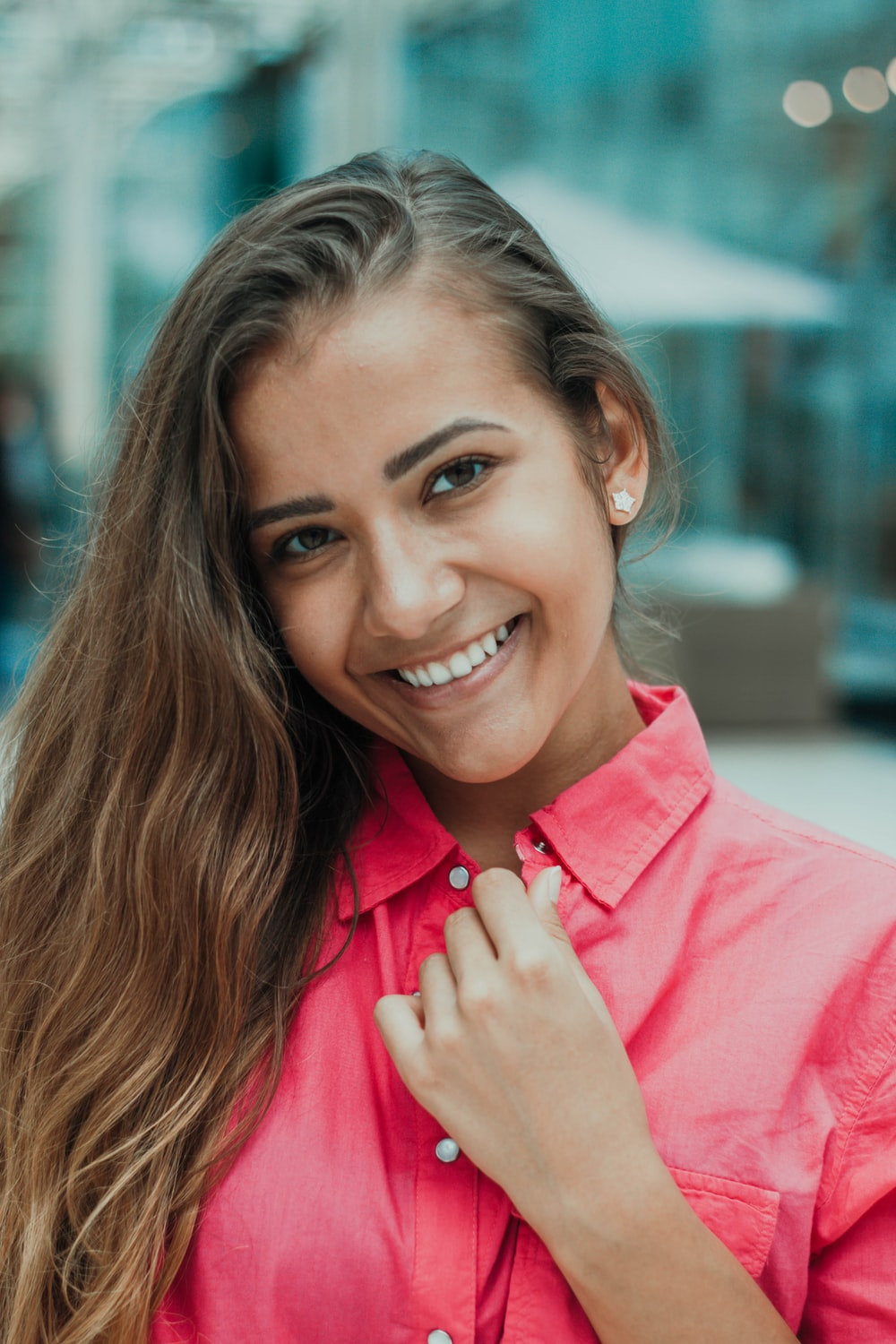 selective focus photography of woman wearing red button-up collared top while smiling