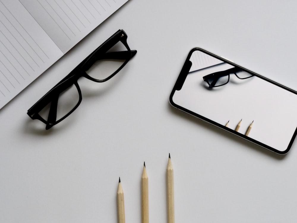 eyeglasses; silver iPhone X; three pencils; notebook flat lay photography