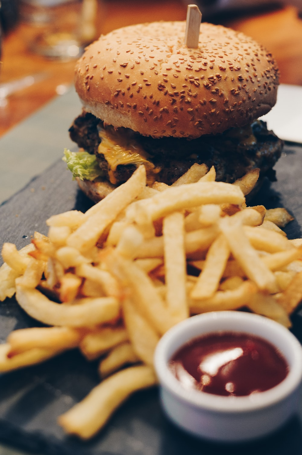 burger with fries on brown wooden plank