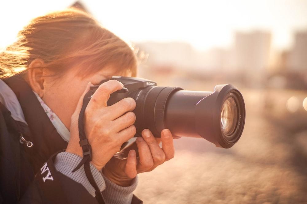 woman using black Sony DSLR camera