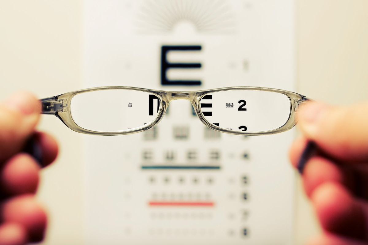 blurred hands holding eyeglasses with a blurred eye chart in the background.  The letters viewed through the eyeglasses are in focus.
