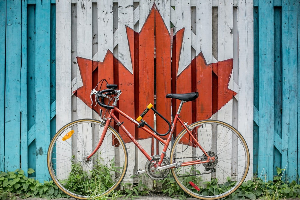 red road bike beside red and white wooden maple leaf painted wall