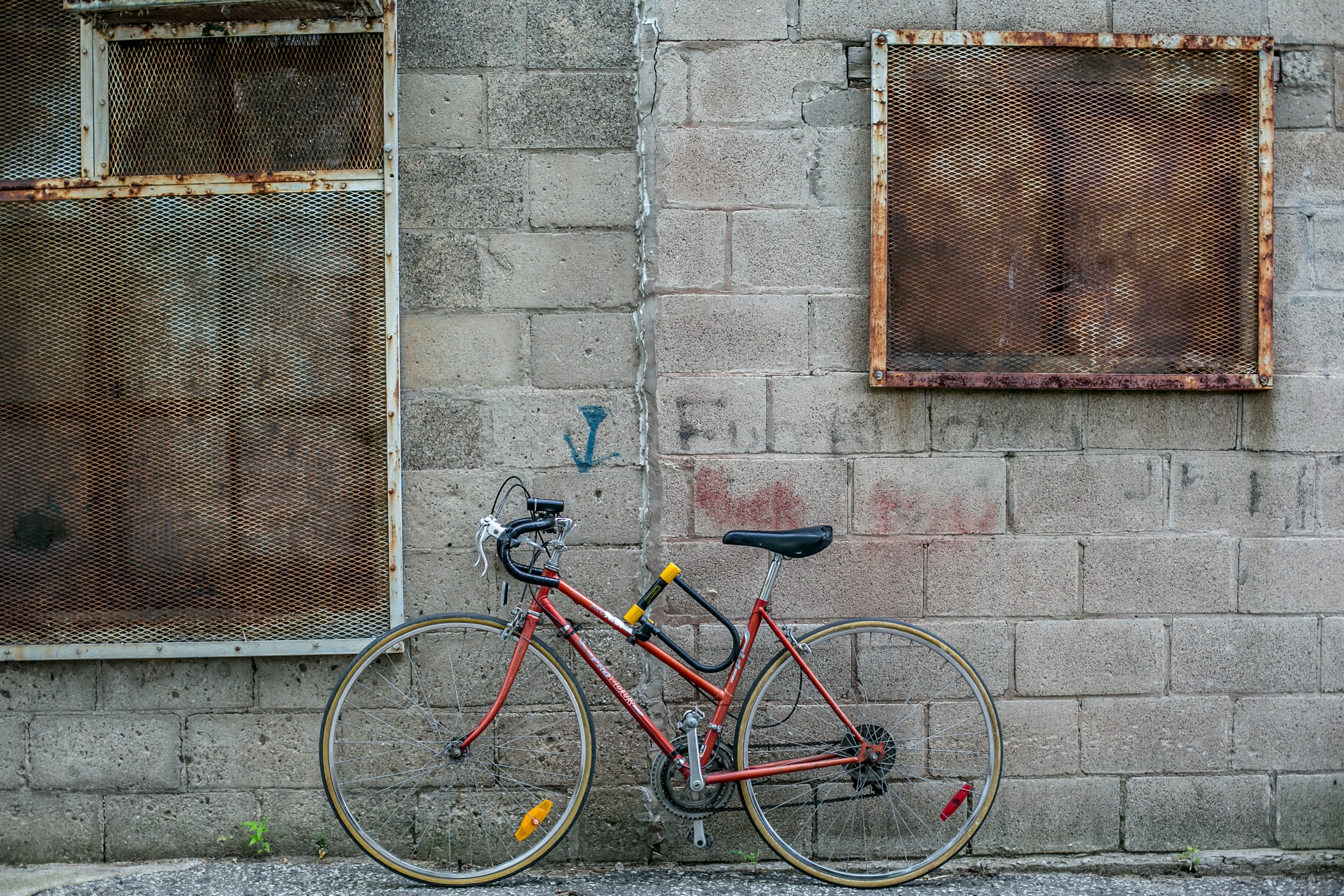 red and black drop-handled road bike leaning on gray concrete wall during daytime