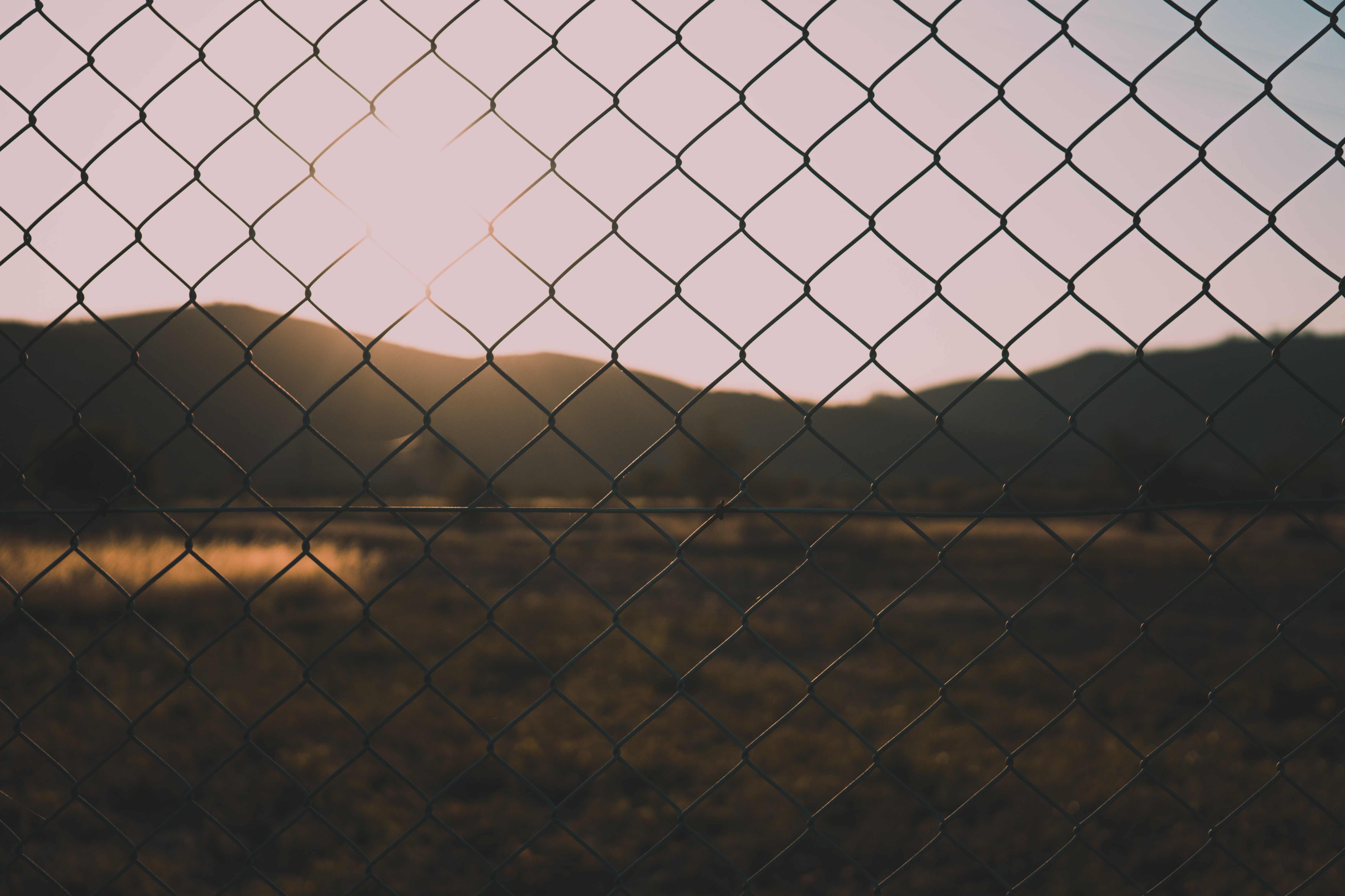 silhouette photography of chain-link fence