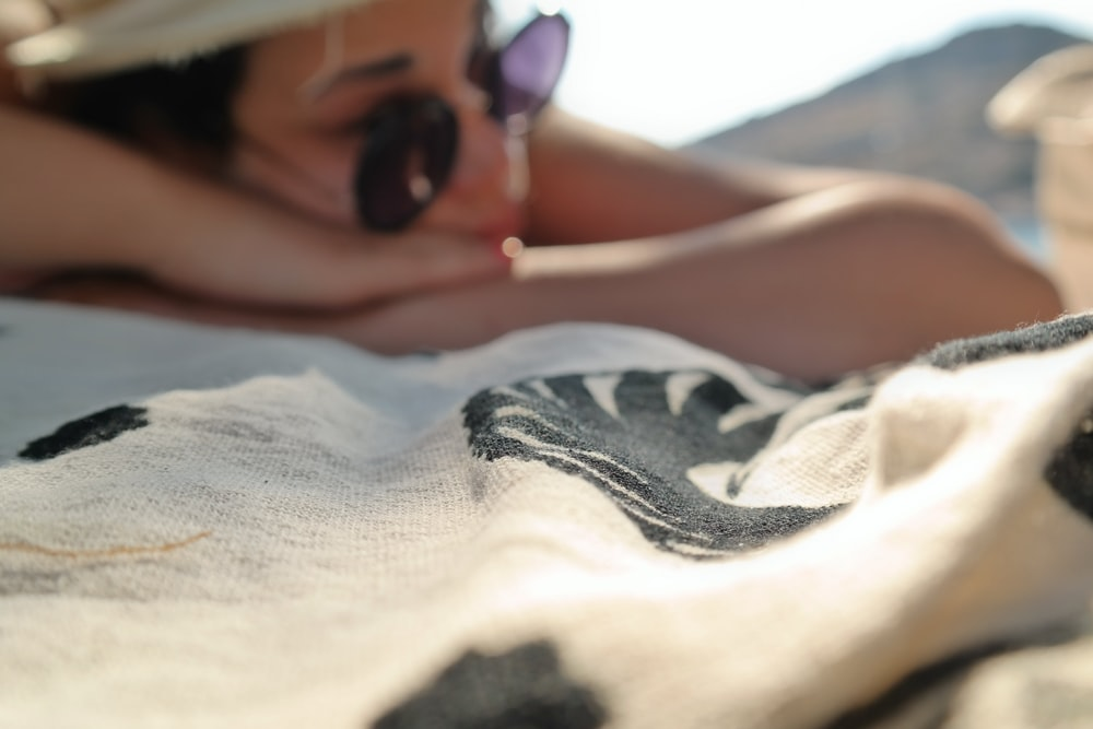 woman lying on white and black textile during daytime