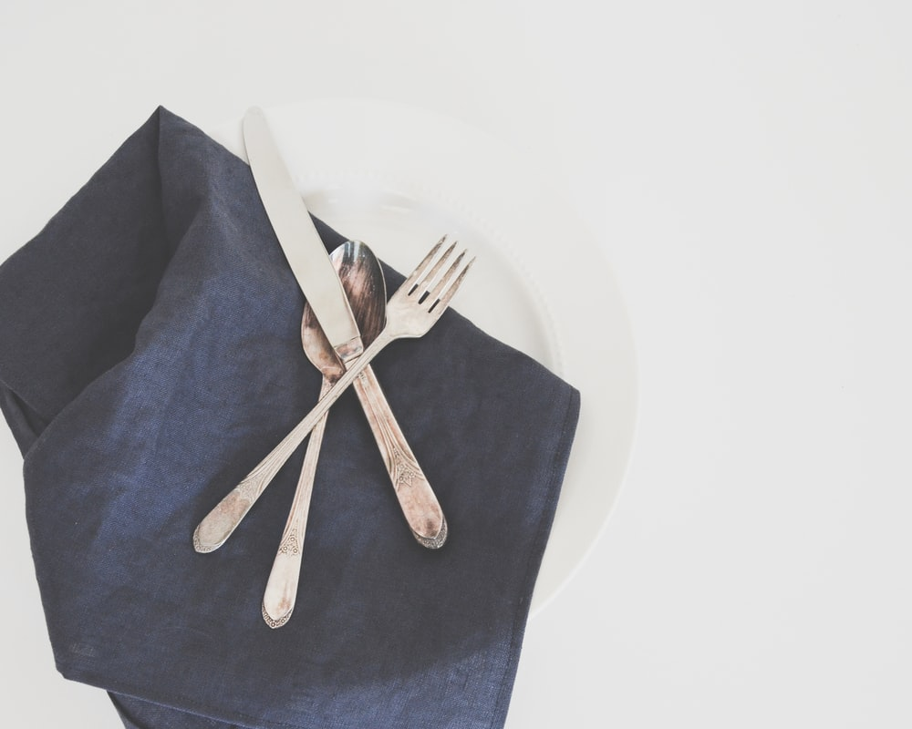 gray fork, spoon, and butter knife on plate with black table napkin
