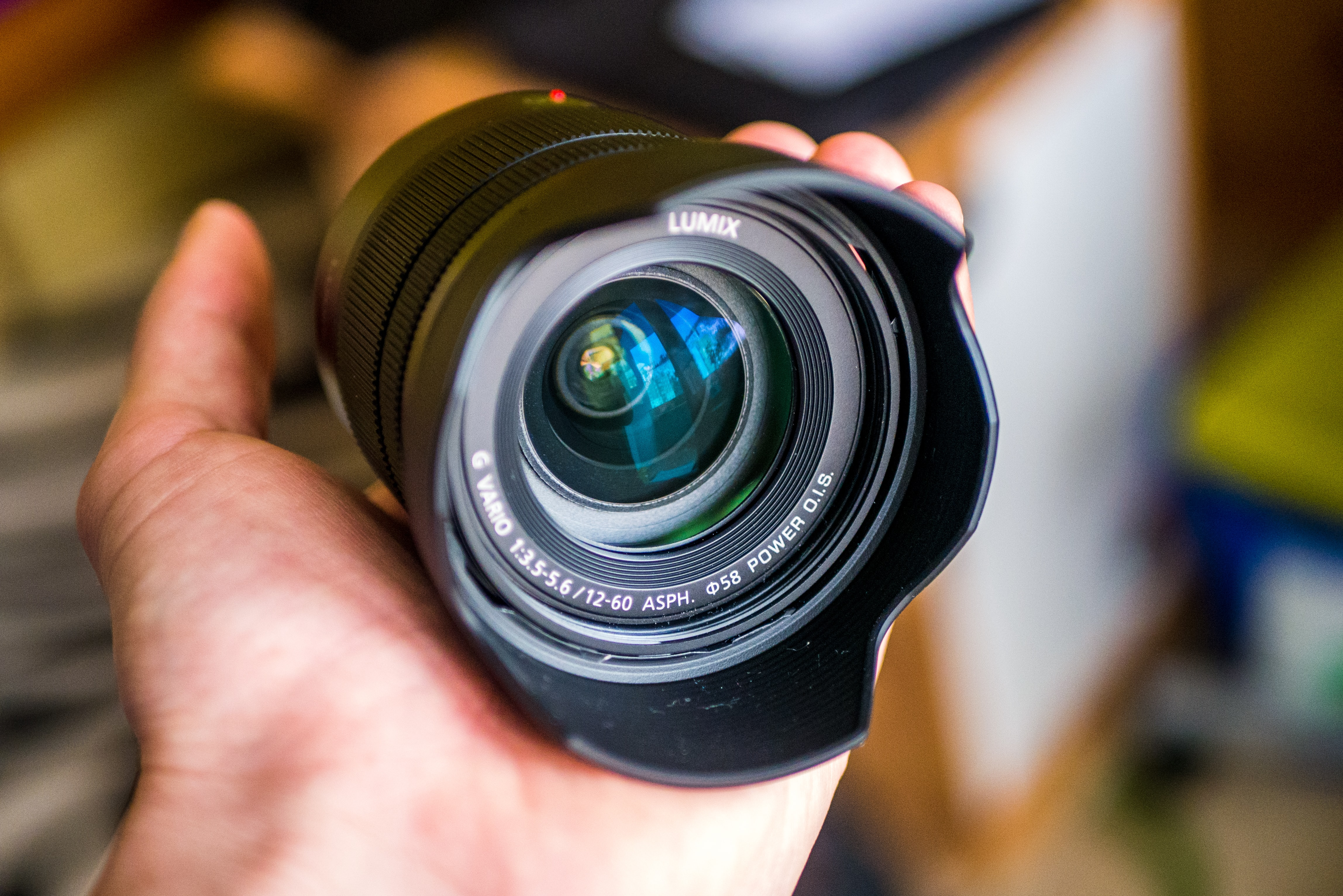 selective focus of person holding Lumix camera lens