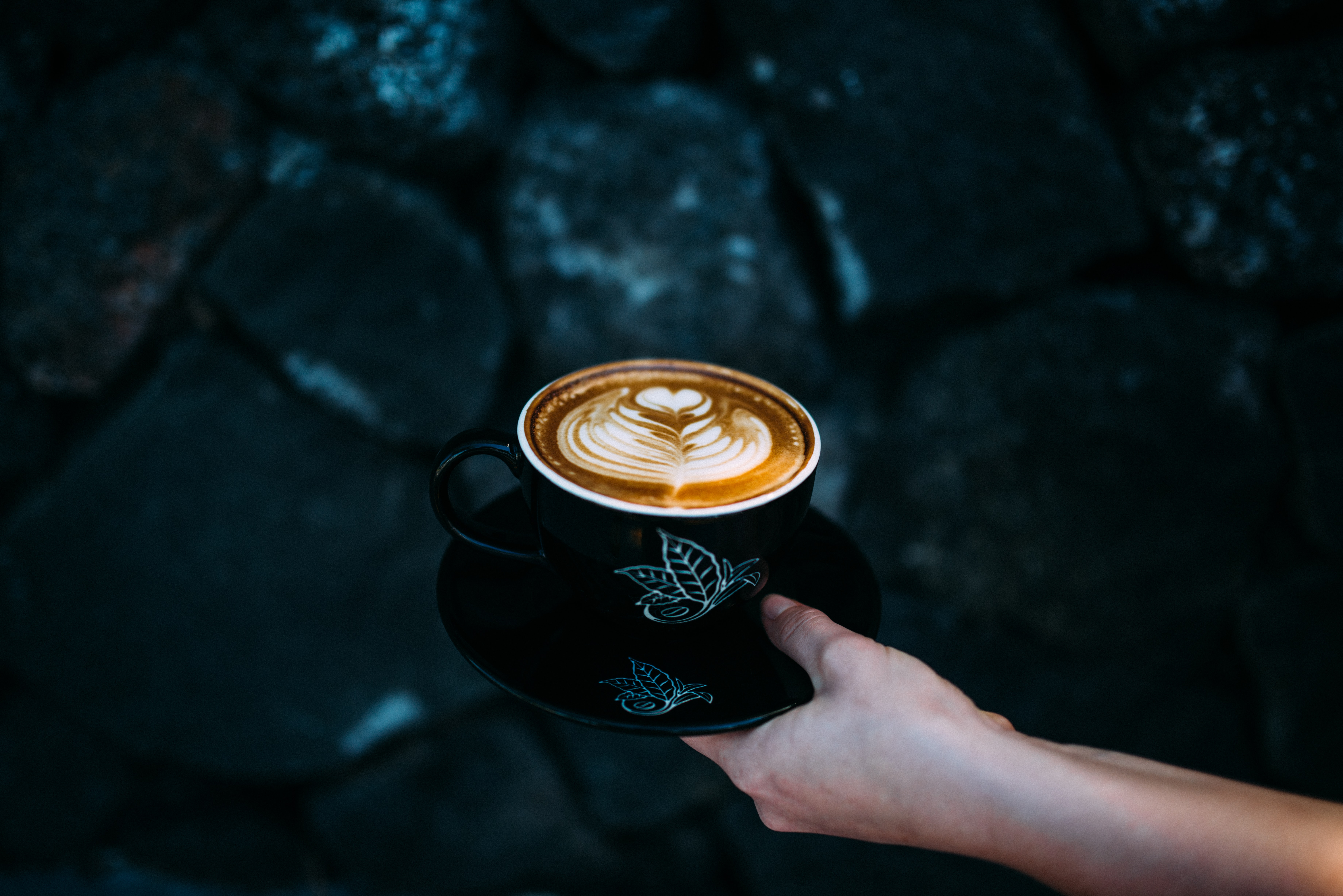 person holding teacup with cappuccino
