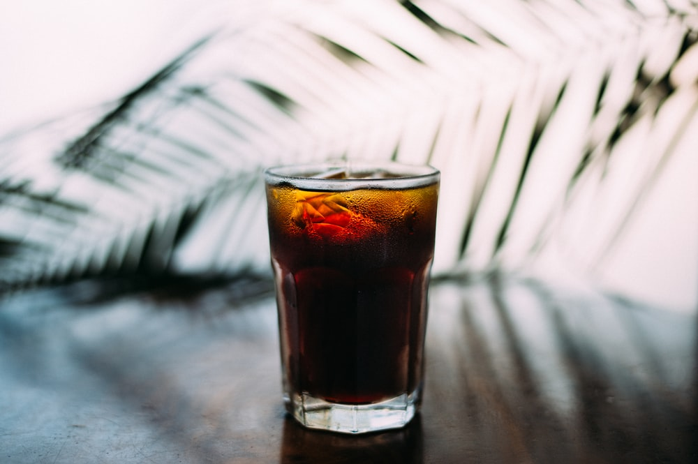 selective focus photo of glass of brown liquid