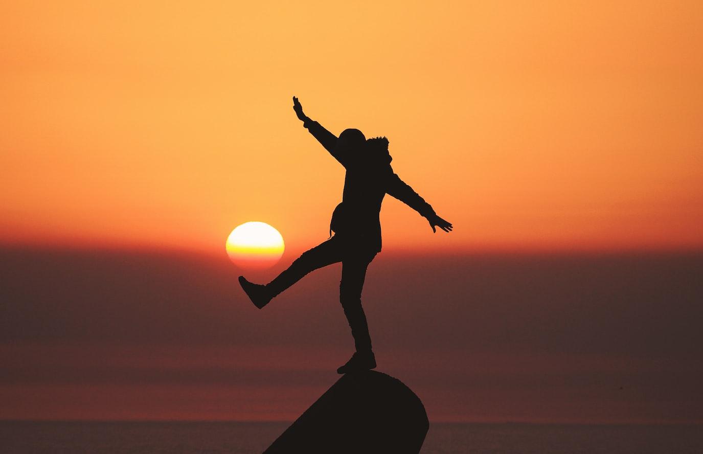 Silhouette einer Person bei Sonnenaufgang