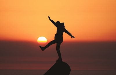 photo of silhouette photo of man standing on rock life zoom background