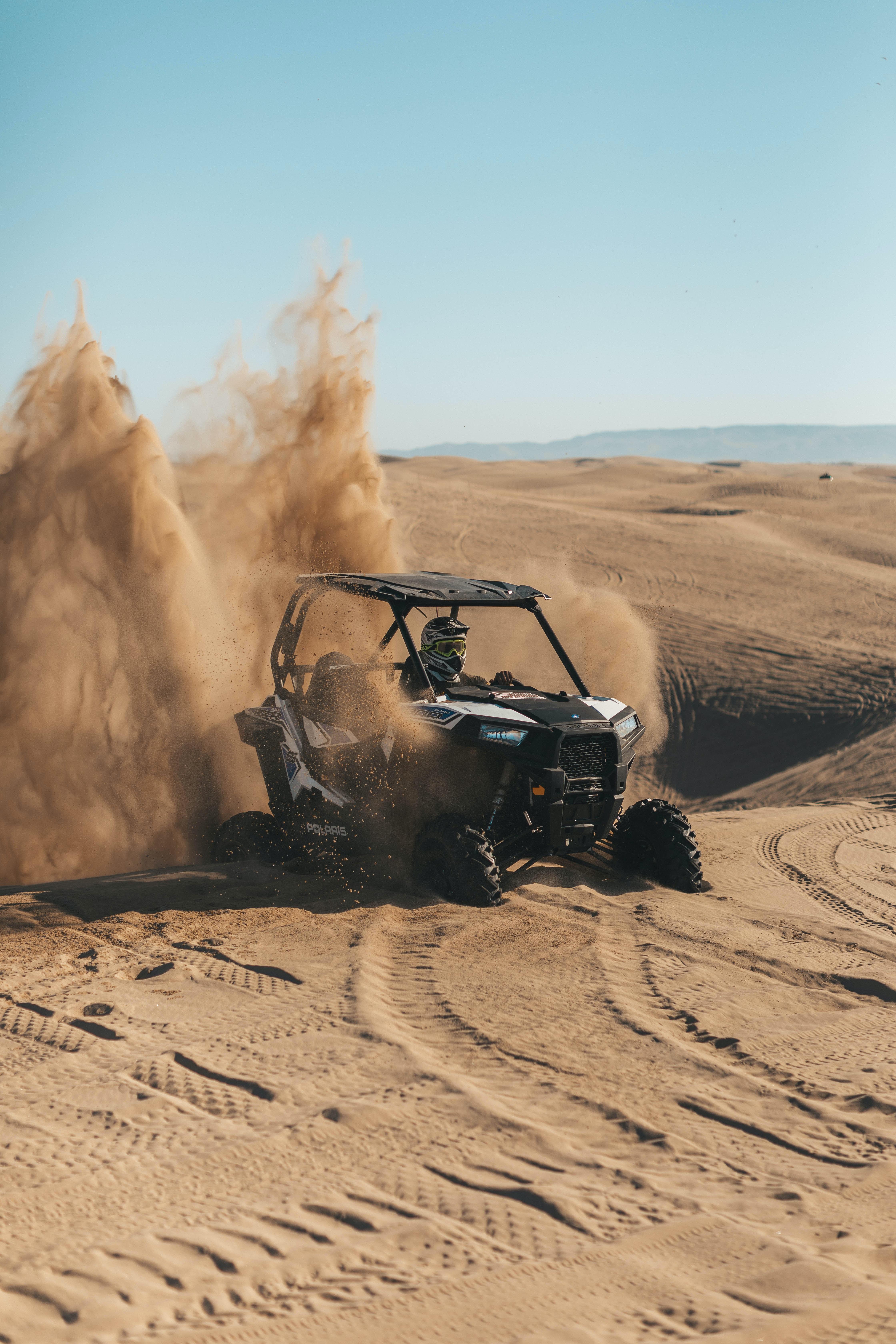 person riding an UTV on desert