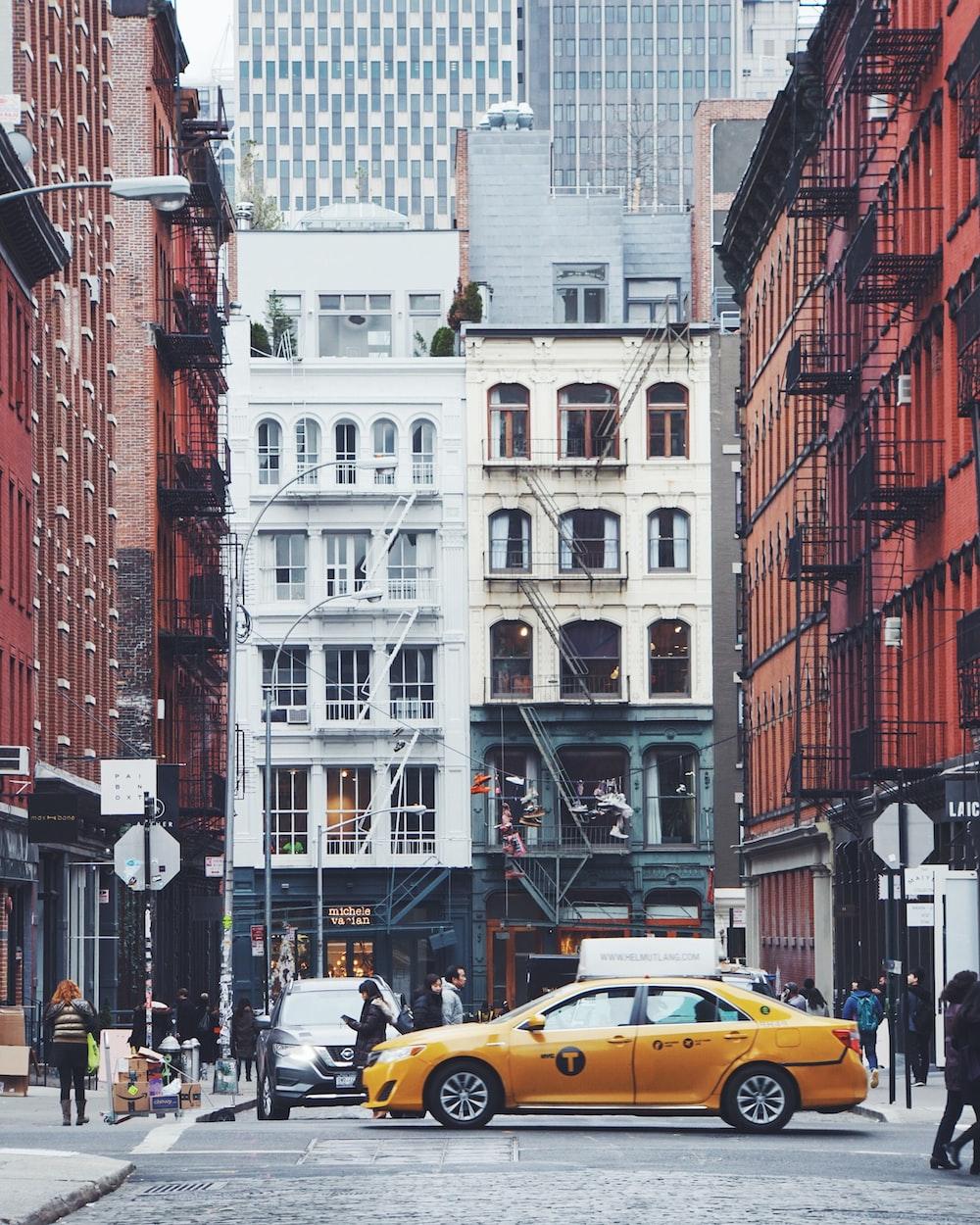 yellow sedan on road near buildings with people walks