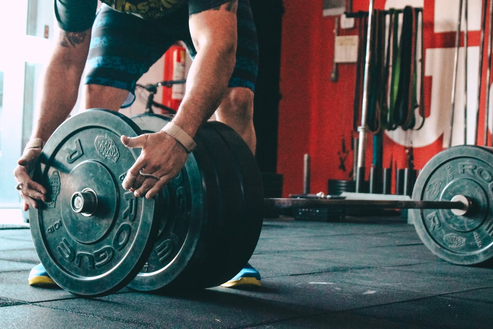 man placing weight plate on barbell