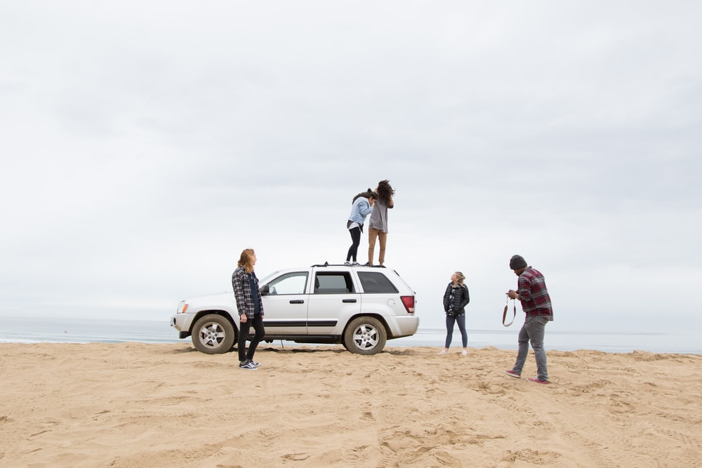 two people standing on Jeep Grand Cherokee SUV while the other person camera on sand during daytime