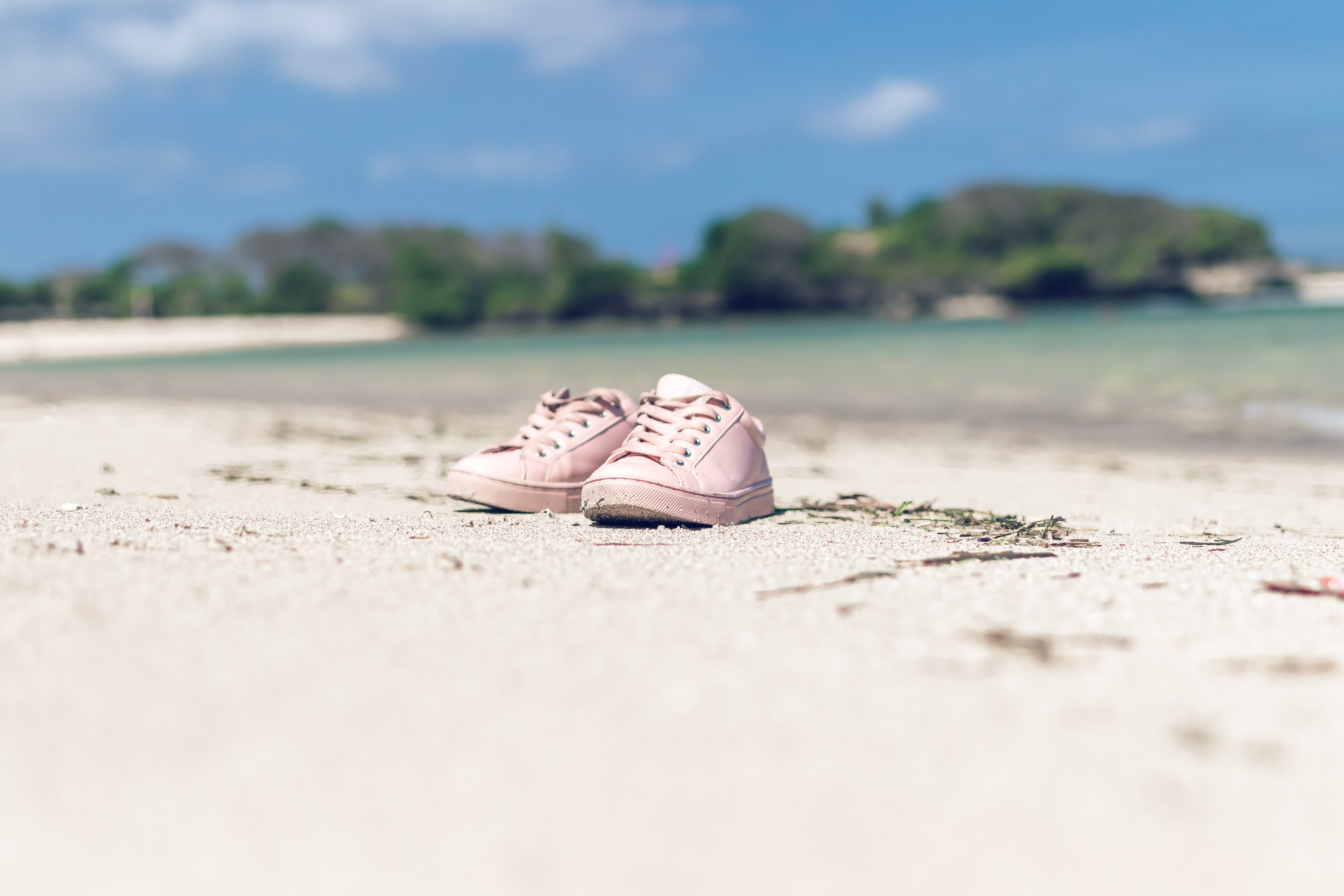 pair of pink shoes on white sand near water during daytime
