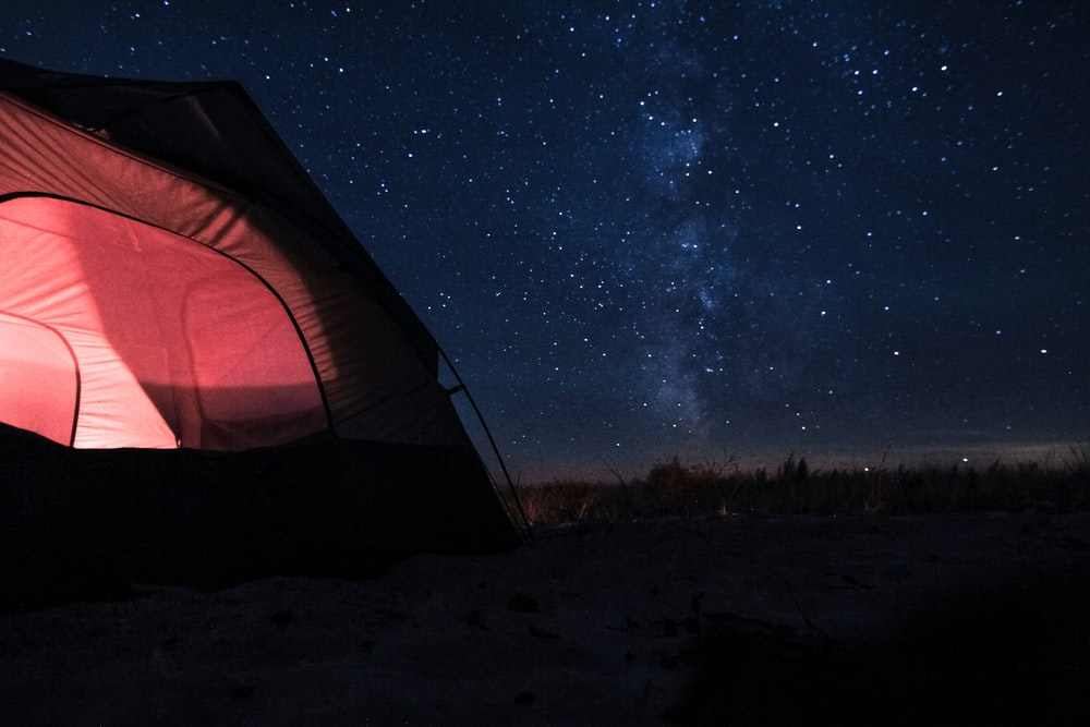 red dome tent with light inside under blue sky with stars during nighttime