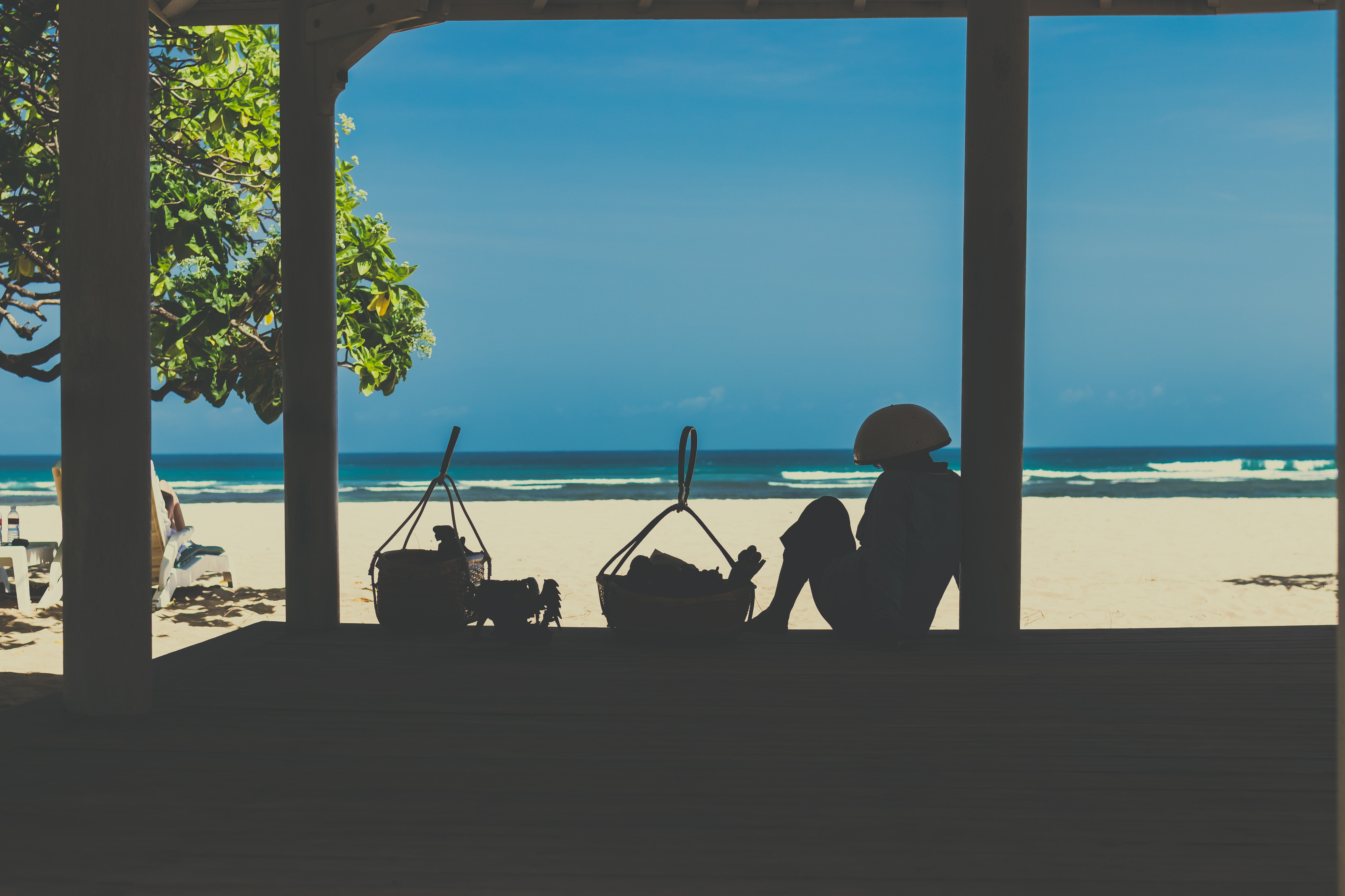 silhouette of person near basket while looking seashore during daytime