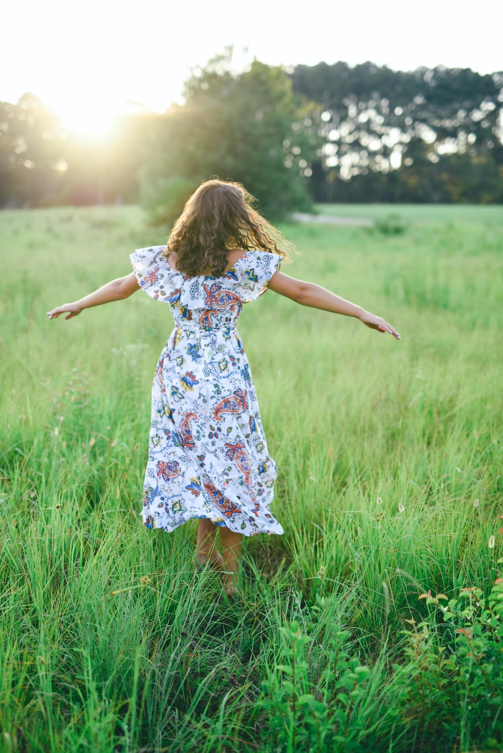 shallow focus photography of woman in white, blue, and green floral dress