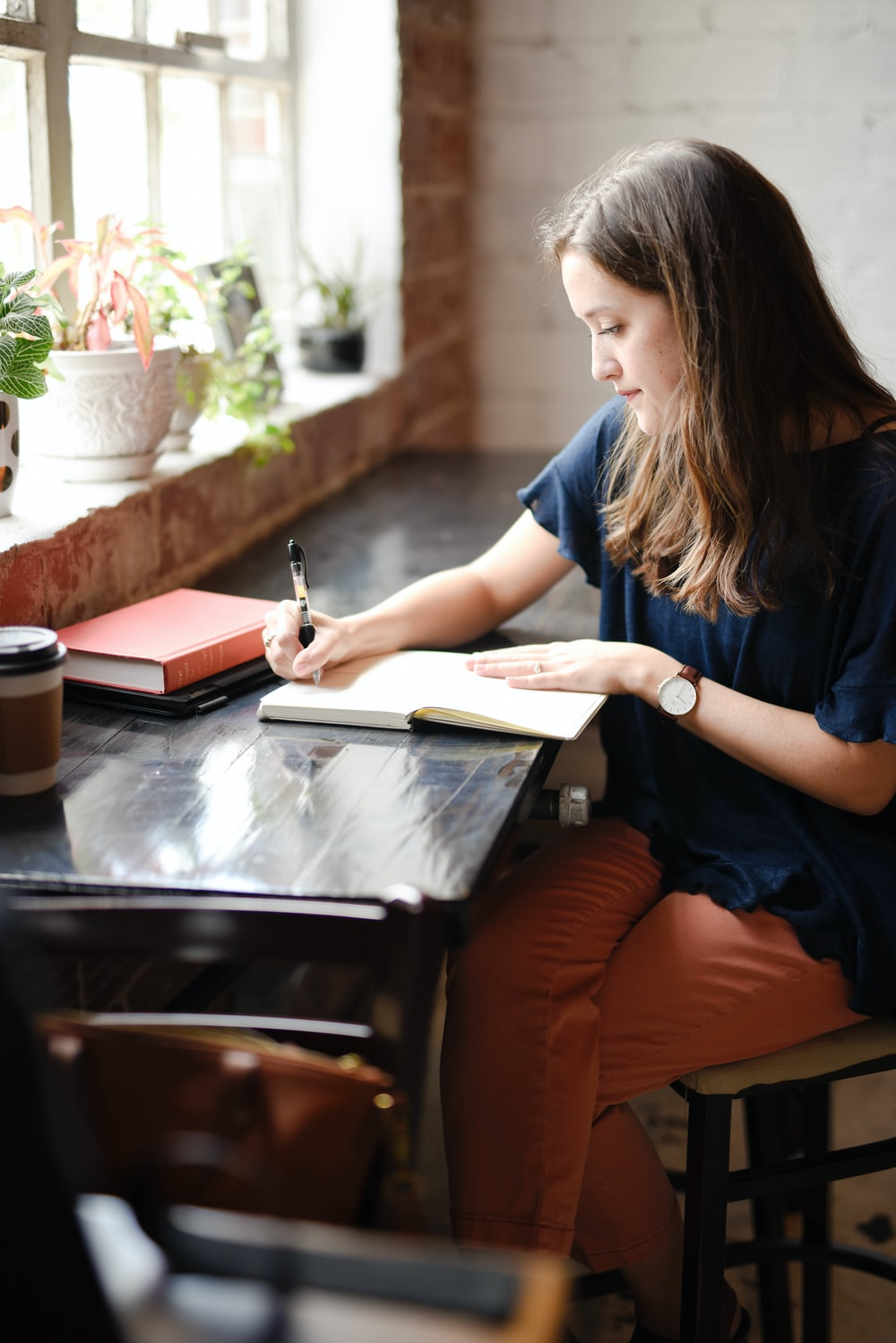 woman sitting in front of black table writing on white book near window