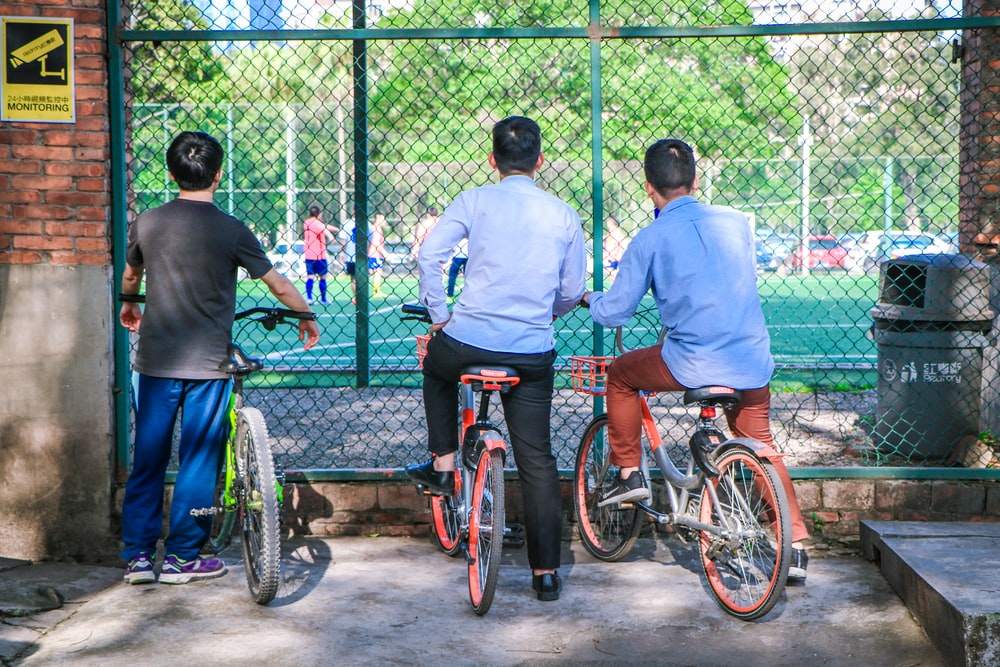 three men sitting on bikes while watching soccer game