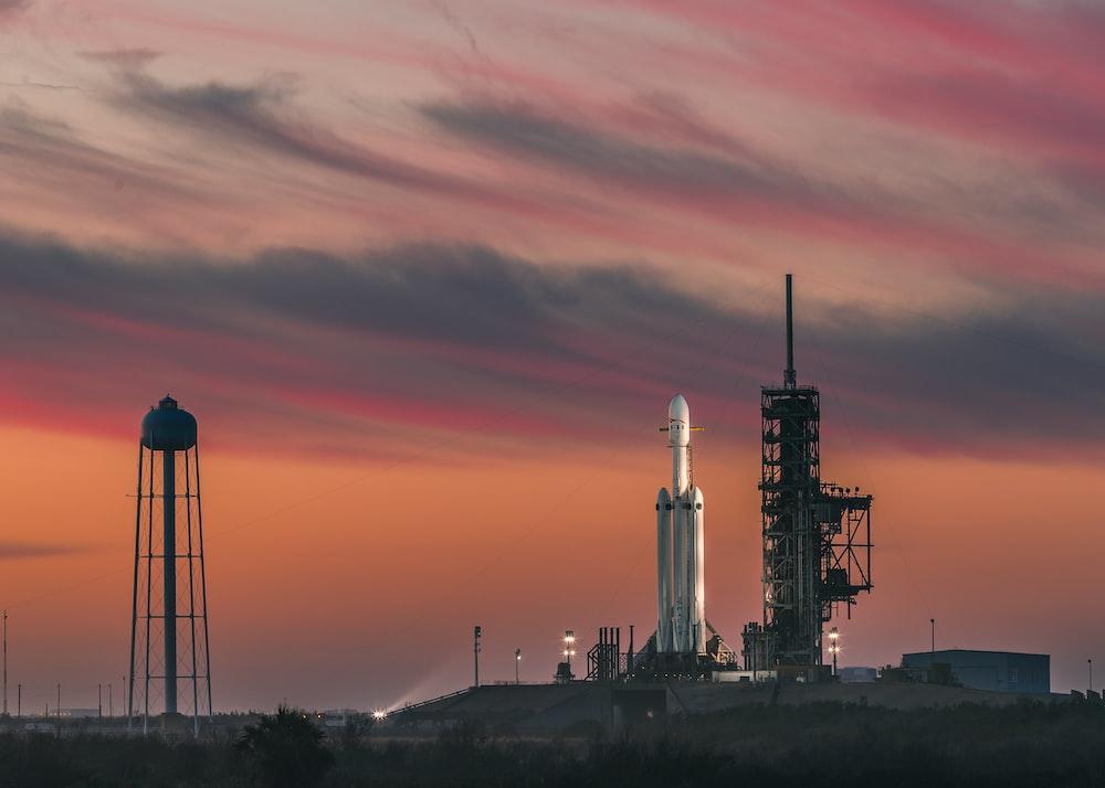 white rocket under nimbus clouds at golden hour