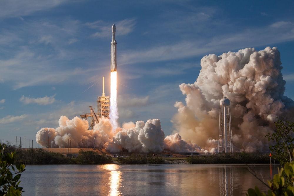gray spacecraft taking off during daytime