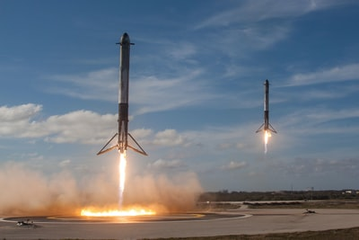 twom white flying rockets during daytime launch day teams background