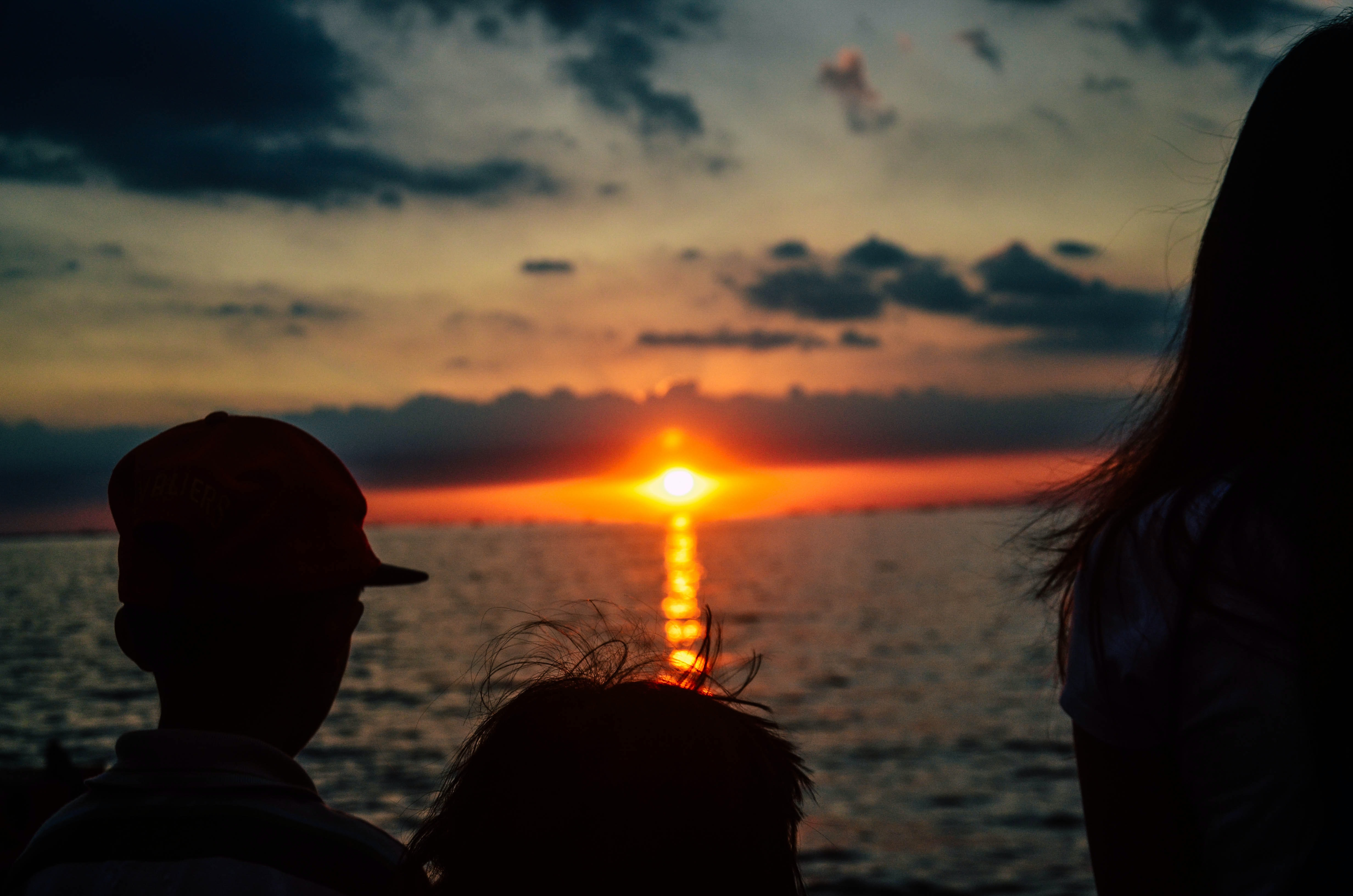 silhouette of children looking on orange sunset above sea
