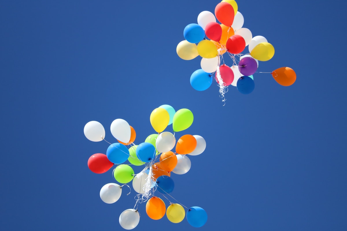 Two colorful bunches of balloons floating away in the sky