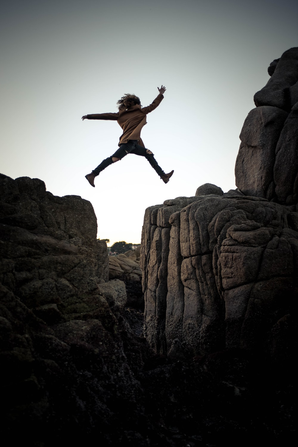 person jumping on big rock under gray and white sky during daytime