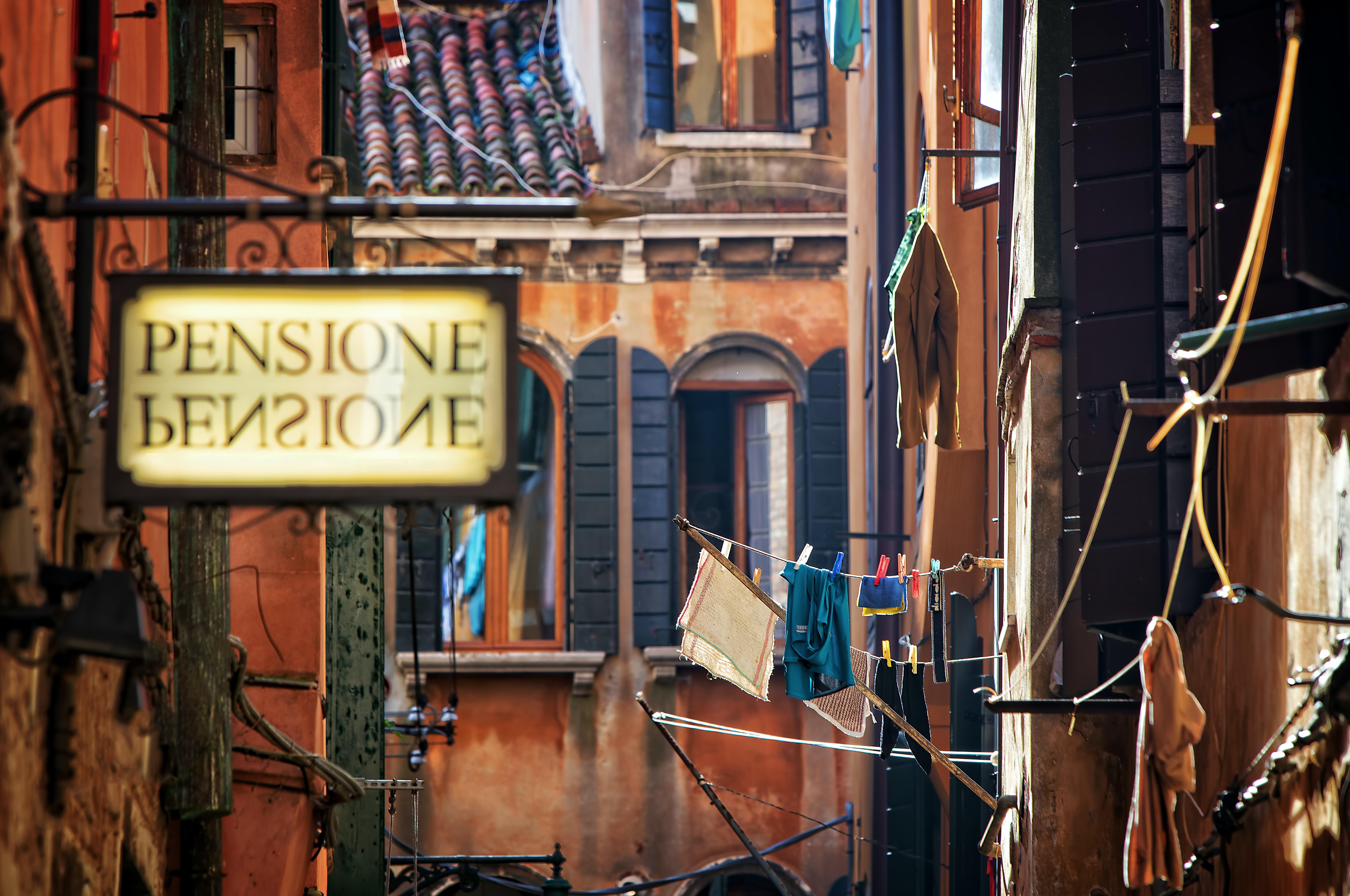 pensione signage near brown concrete building