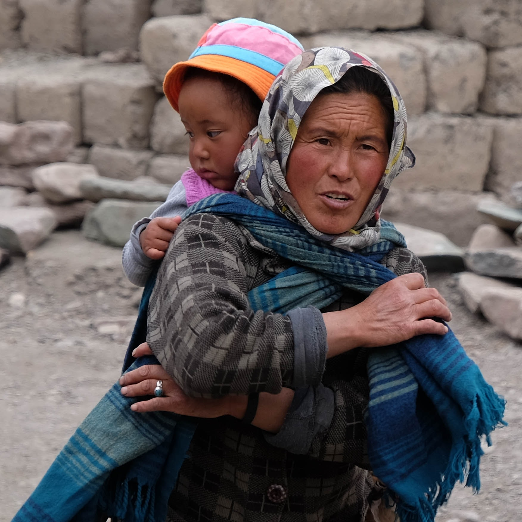 woman wearing scarf while carrying a girl at her back during daytime