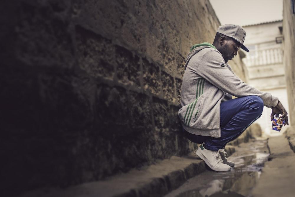 man sitting against wall