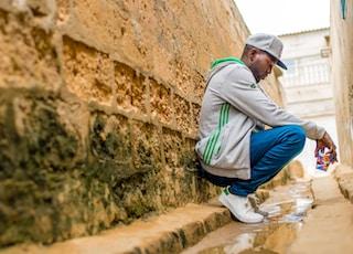 man sitting beside wall during daytime