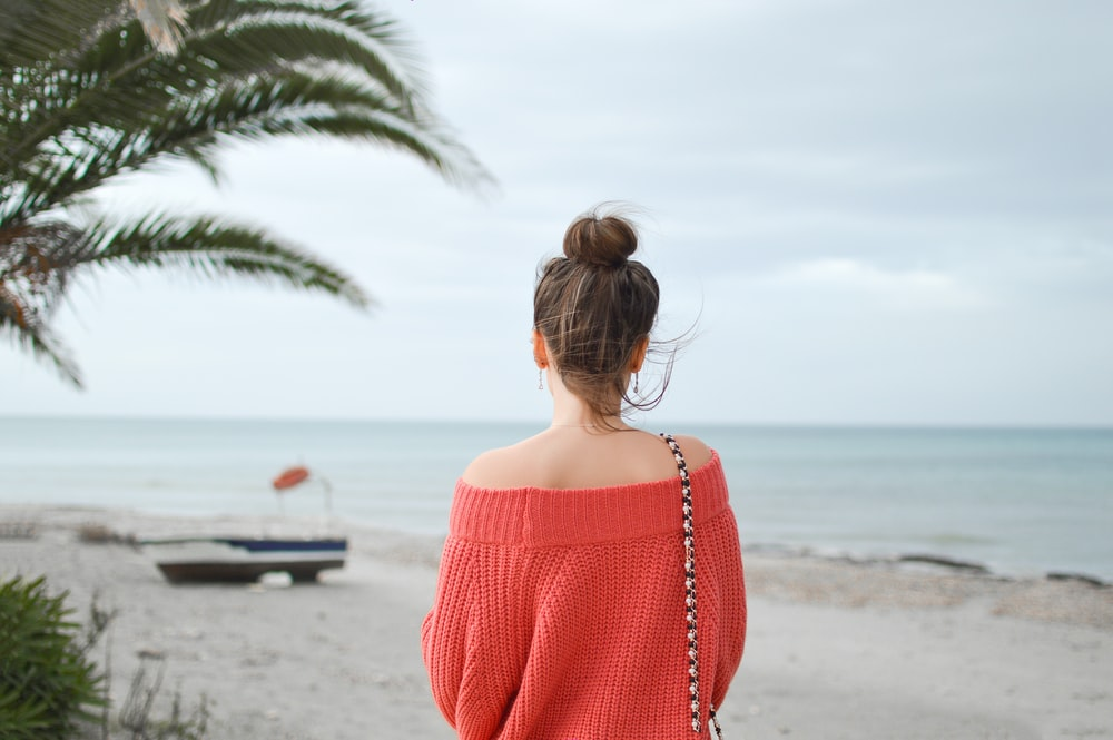woman wearing red knitted sweater standing on the beach
