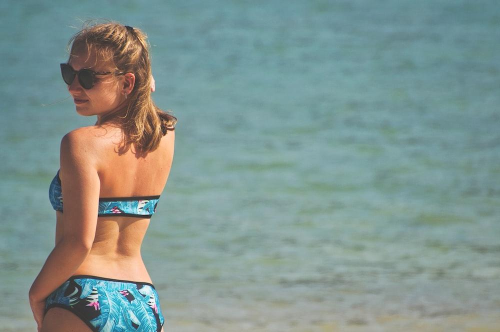 248f53edff61d woman in blue bikini poking on camera near beach