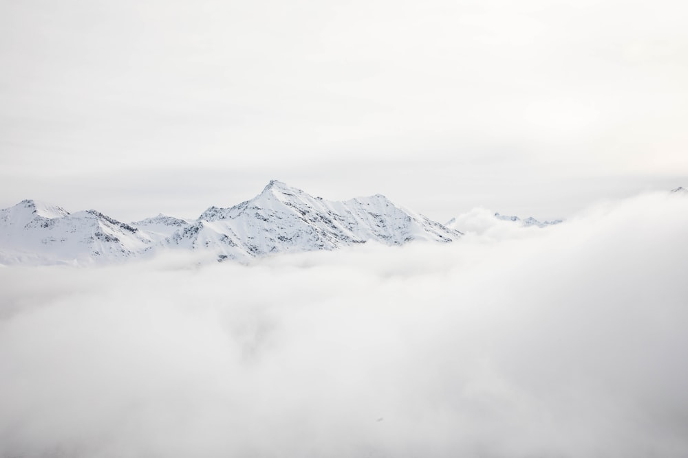 mountain range covered with snow and clouds at daytime